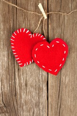 Two Valentines Day cloth hearts hanging on old wood