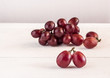Red grapes on wooden table background