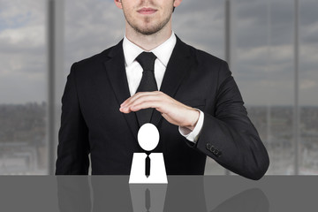 businessman holding protective hand above employee