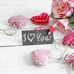 "blackboard ""I love you"" with  red vintage hearts and old wooden"