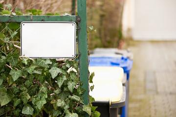 Leeres weisses Schild an einem Zaun