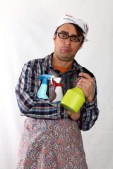 Mann hält ratlos Putzflaschen,Kopftuch,Schürze