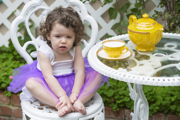 toddler sitting in garden with teapot