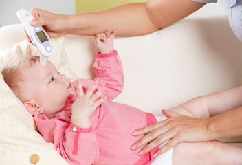 Closeup of a baby with a digital thermometer
