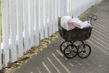 vintage stroller in front of white fence