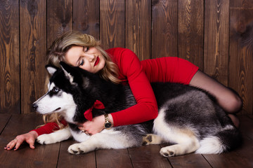 Young girl wearing red dress with her husky dog