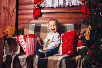 Kid sitting and smiling near Christmas tree