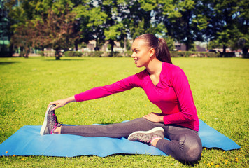 smiling woman stretching leg on mat outdoors