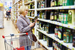 Woman reading label on bottle of olive oil in store - 75959891