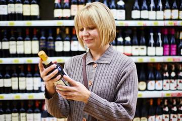 Woman reading label on bottle of wine in store