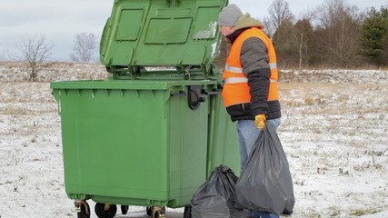 Worker with garbage bags near the container in winter