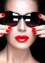 Woman Face with Oversized Sunglasses. Red lips and Manicure