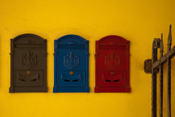 Colorful mailboxes on a yellow wall