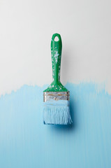 Paintbrush with blue paint streaks