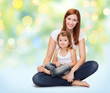 happy mother with little girl over green lights