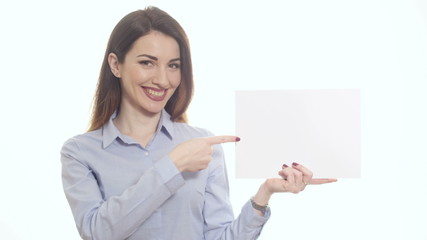 smiling woman blue shirt pointing blank piece paper copy space