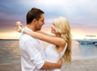 happy couple hugging over sunset beach background