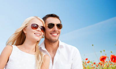 happy couple in shades over poppy field background