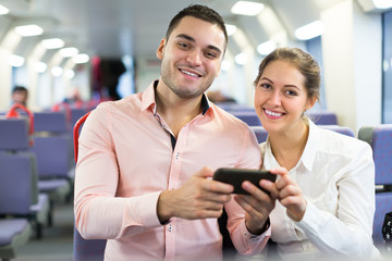 Young couple with smartphones in train