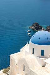 Blue cupola of whitewashed Oia church in Santorini