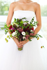 Unusual wedding bouquet with succulent flowers at hands of a bri