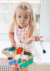 Cute little girl drawing paints