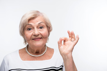 Elderly lady showing OK sign