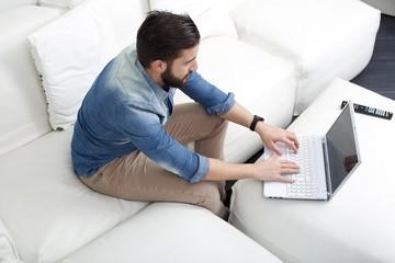 man typing on sofa