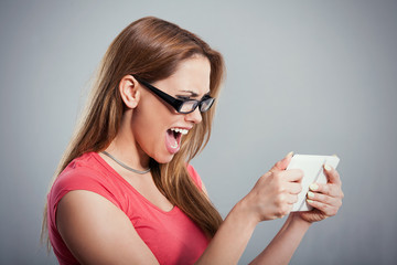 Beautiful young woman shouting on a digital tablet.