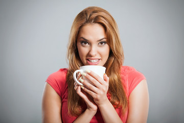 Portrait of a young woman having a cup of hot drink.