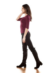 Side view of young woman in boots posing on a white background
