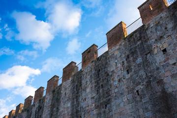 Mura medievali di Pisa, pietre, merli e cielo