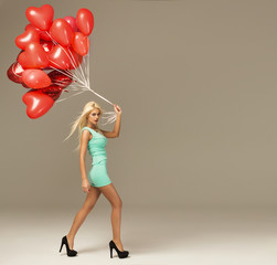 Beautiful blond woman in motion with red balloons