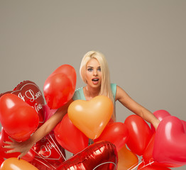 Blond surprised woman with red balloons heart