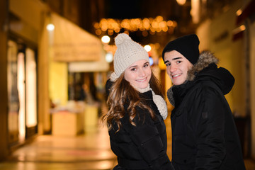 happy young couple having fun in town at night during winter