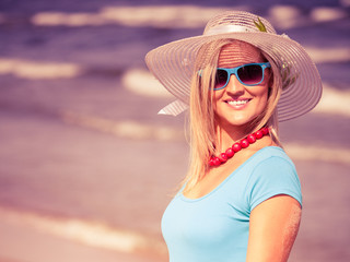Beautiful blonde girl in hat on beach