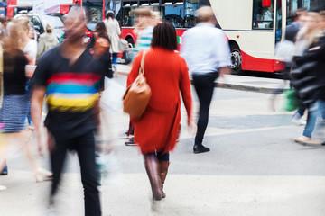Menschen in Bewegungsunschärfe überqueren die Straße
