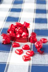 Heart shaped sweet chocolates in red metal box. Closeup.