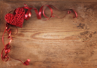 Heart and ribbon on the old wooden board