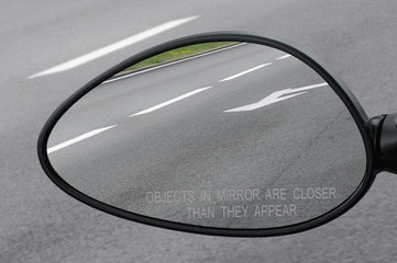 Rear view mirror with warning text objects in mirror are closer
