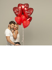 Young couple with red balloons heart and white empty space