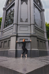 Ballerina en pointe near black wall