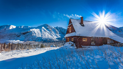 Mountain small cottage in a winter dawn