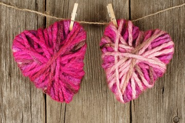 Two Valentines Day wool hearts on clothesline on old wood