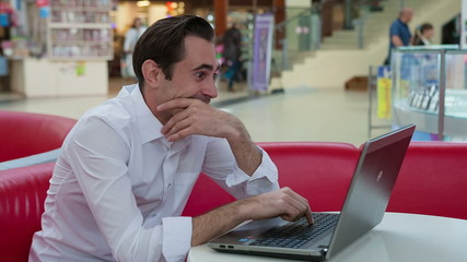 Young handsome man talking over laptop showing humorous tongue