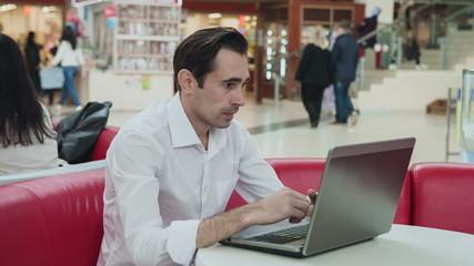 Senior business person in white shirt sitting at caffe desk