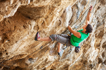 Rock climber going to clip rope while lead climbing