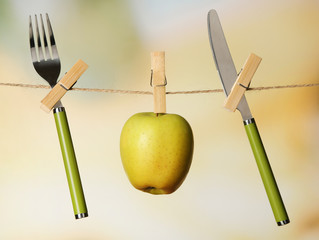 Fork, knife and apple hanging from clothesline