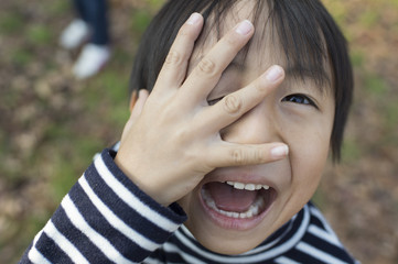 Child is laughing while covering her face with hand
