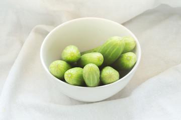 fresh green cucumbers on white fabric background